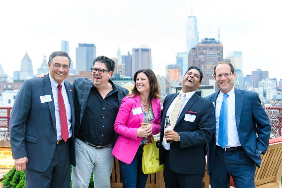 Alumni at event in Philadelphia with the city skyline in the background