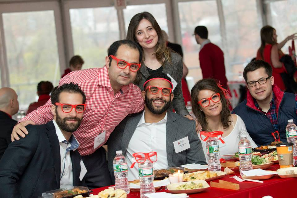Alumni sitting at a table wearing Temple glasses.